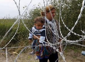 A Syrian migrant carries a child while standing behind…