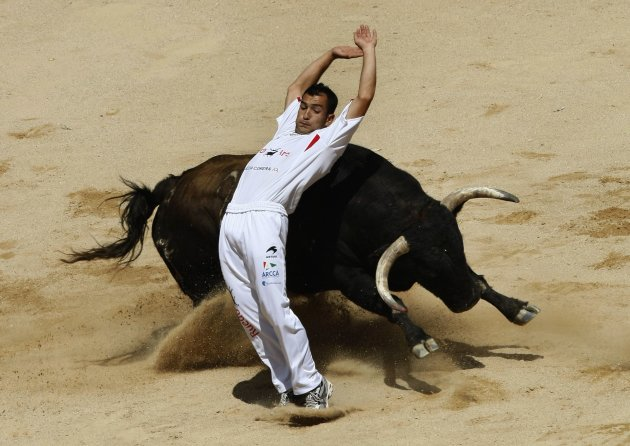 A recortador performs a pass during a contest at Pamplona's bullring on the third day of the San Fermin festival