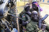 South Sudan army soldiers hold their weapons as they smile in Malakal town, 497km (308 miles) northeast of capital Juba, December 30, 2013 after retaking the town from rebel fighters. REUTERS/James Akena
