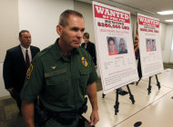 As they walk by wanted posters, Richard Barlow, front, Chief of the Tucson Sector of U.S. Customs and Border Protection Border Patrol, James L. Turgal, Jr., left, FBI Special Agent in Charge, and Laura E. Duffy, United States Attorney Southern District of California, leave a news briefing after it was announced that an indictment on five suspects related to the death of U.S. Border Patrol agent Brian Terry, Monday, July 9, 2012, in Tucson, Ariz. A reward of up to $1 million dollars for information leading to the arrest of four fugitives was also announced by Department of Justice officials.(AP Photo/Ross D. Franklin)