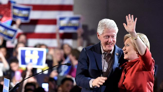 Democratic presidential candidate Hillary Clinton (R) and husband Bill Clinton (L) wave to a cheering crowd after winning the Nevada democratic caucus at Caesar's Palace in Las Vegas, Nevada on February 20, 2016