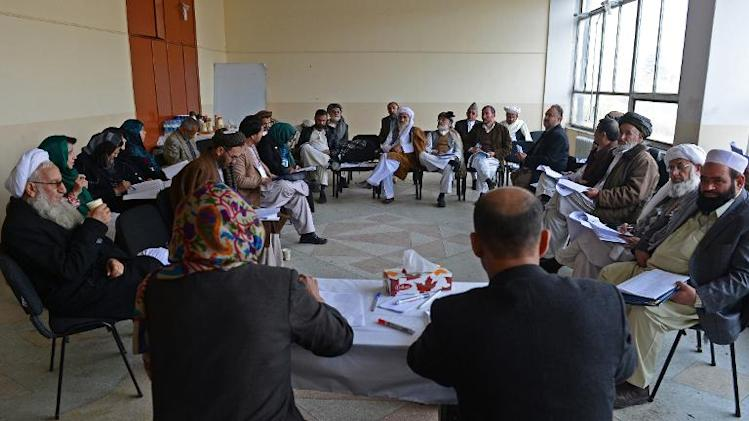 Afghan delegates discuss the Bilateral Security Agreement during a four-day loya jirga, a meeting of Afghan tribal elders and leaders, in Kabul on November 22, 2013