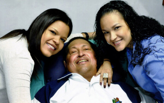 Venezuela's President Hugo Chavez smiles in between his daughters, Rosa Virginia (R) and Maria while recovering from cancer surgery in Havana in this photograph released by the Ministry of Information on February 15, 2013. Venezuela's government published the first pictures of cancer-stricken Chavez since his operation in Cuba more than two months ago, showing him smiling while lying in bed reading a newspaper, flanked by his two daughters. The 58-year-old socialist leader had not been seen in public since the Dec. 11 surgery, his fourth operation in less than 18 months. The government said the photos were taken in Havana on February 14, 2013.   REUTERS/Ministry of Information/Handout (VENEZUELA - Tags: POLITICS PROFILE TPX IMAGES OF THE DAY HEALTH)  ATTENTION EDITORS - THIS IMAGE WAS PROVIDED BY A THIRD PARTY. FOR  EDITORIAL USE ONLY. NOT FOR SALE FOR MARKETING OR ADVERTISING CAMPAIGNS. THIS PICTURE IS DISTRIBUTED EXACTLY AS RECEIVED BY REUTERS, AS A SERVICE TO CLIENTS
