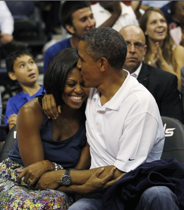 U.S. President Barack Obama kisses first lady Michelle Obama during the Olympic men's exhibition basketball game between Team USA and Brazil in Washington