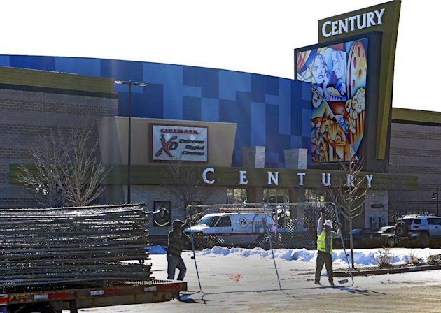 "Workers with American Fence remove the fence from around the Century theater in Aurora, Colo., on Thursday, Jan. 17, 2013. The Colorado movie theater where a gunman killed 12 people and wounded dozens of others reopens Thursday with a private ceremony for victims, first responders and officials. Theater owner Cinemark plans to temporarily reopen the entire 16-screen complex in Aurora to the public on Friday, then permanently on Jan. 25. Aurora's mayor, Steve Hogan, has said residents overwhelmingly support reclaiming what he calls ""an important venue for Aurora."" (AP Photo/Ed Andrieski)"