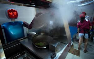 A robot cooks vegetables in a kitchen of a restaurant …