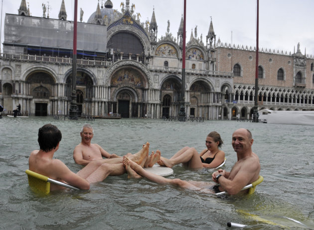 People sit at the table of a bar in a flooded St. Mark's Square in Venice, Italy, Sunday, Nov. 11, 2012. High tides have flooded Venice, leading Venetians and tourists to don high boots and use wooden