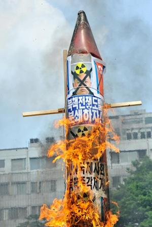 South Korean conservative activists burn a mock missile …