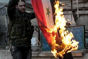 A rebel fighter burns a Syrian flag found in a building…