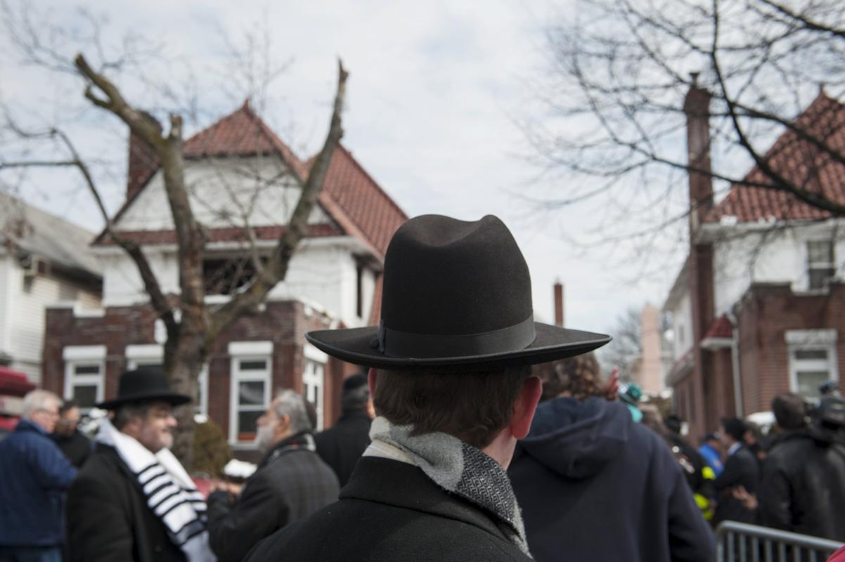 Community members stand at the site of a home fire in the Midwood neighborhood of Brooklyn, New York
