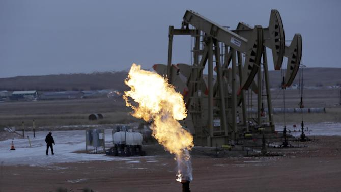 In this Dec. 17, 2014 photo, workers tend to oil pump jacks behind a natural gas flare near Watford City, N.D. Natural gas, the nation's most prevalent heating fuel, is getting cheaper just as winter is arriving because of mild temperatures and plentiful supplies. (AP Photo/Eric Gay)