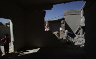 Syrians clear the rubble of a house was destroyed in government airstrike on Saturday, in Kal Jubrin, on the outskirts of Aleppo, Syria, Sunday, Sept. 16, 2012. (AP Photo/Muhammed Muheisen)