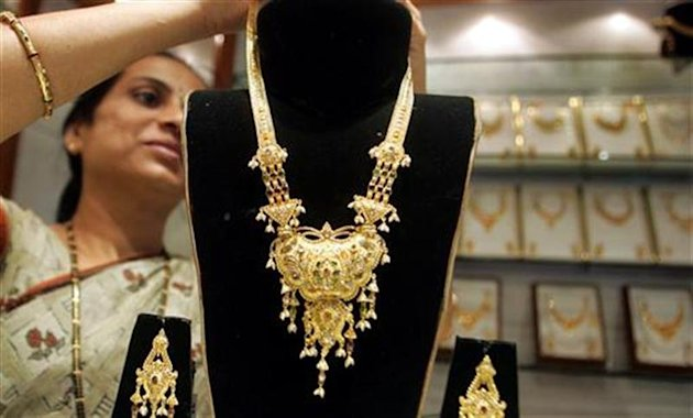 Worker displays gold jewellery at shop in Mumbai