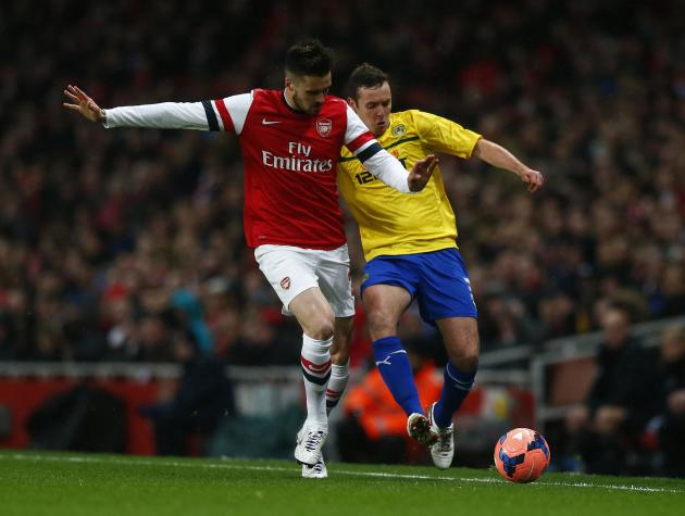 Arsenal's Carl Jenkinson is challenged by Coventry City's Blair Adams during their English FA Cup fourth round soccer match at The Emirates in London