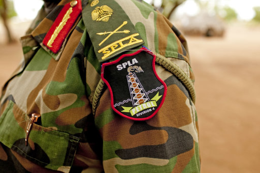 A Sudan People's Liberation Army (SPLA) commander dons the new insignia of the 4th Division petroleum defense unit in Bentiu, Unity State, South Sudan on Friday, May 11, 2012. In late April, tensions between Sudan<br /><br /><br /><br /><br /><br /><br /><br /><br />  and South Sudan erupted into armed conflict along their poorly defined border. Thousands of SPLA forces have been deployed to Unity State where the two armies are at a tense stalemate around the state's expansive oil fields. Fighting between the armies lulled in early May after the U.N. Security Council ordered the countries to resume negotiations. South Sudan seceded from the Republic of Sudan in July 2011 following decades of civil war. (AP Photo/Pete Muller)