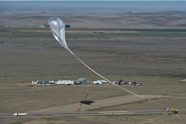 Handout photo of the crane following the balloon with the capsule at the flight line during the final manned flight for Red Bull Stratos in Roswell