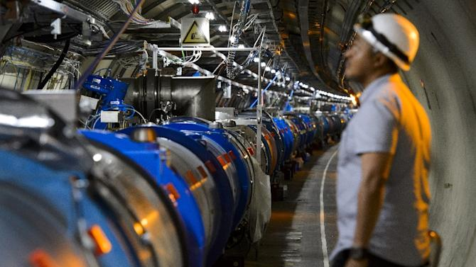 A scientist looks at a section of the European Organisation for Nuclear Research (CERN) Large Hadron Collider (LHC) in Meyrin, near Geneva, during maintenance works on July 19, 2013