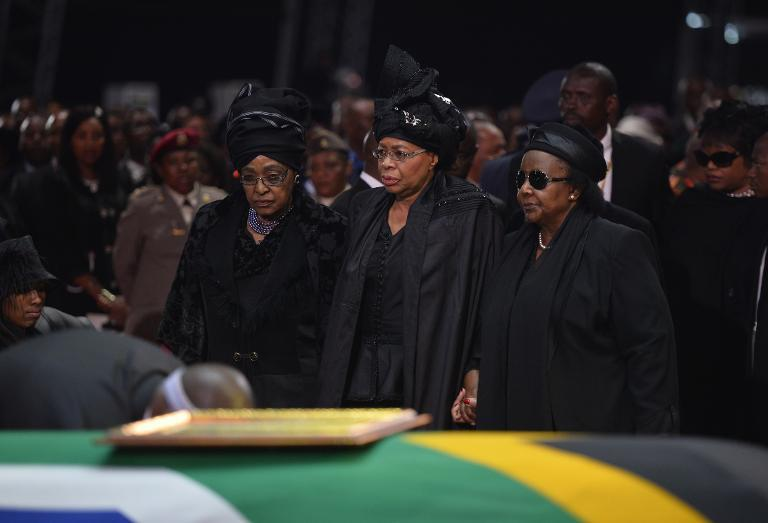 Winnie Mandela Madikizela (L) and Graca Machel (C) stand by the coffin of Nelson Mandela during his funeral ceremony in Qunu on December 15, 2013