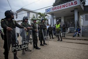 Police stand guard in front of the hospital in Carmen…