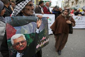 Palestinian supporters of the Fatah movement hold placards…