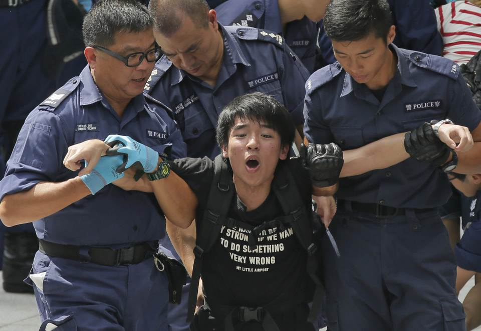 A student is taken away by policemen at the government headquarter  in Hong Kong, Saturday, Sept. 27, 2014. Riot police in Hong Kong on Saturday...