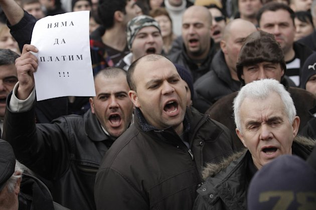 "Bulgarians shout slogans and one holding a note reading ""We will not pay"" during a protest against higher electricity and heating bills, in Sofia, Sunday, Feb. 17, 2013. Thousands of angry Bulgarians chanted ""mafia"" and ""resignation"" demanded the expulsion of the three foreign-controlled power distributors that control the local market: Czech Republic's CEZ and Energo-Pro, and Austria's EVN (AP Photo/Valentina Petrova)"
