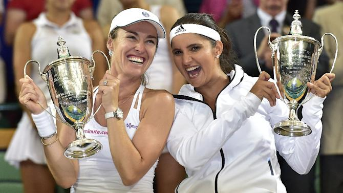 Switzerland's Martina Hingis (L) and India's Sania Mirza pose with the winner's trophies during the presentation after winning the women's doubles final on day twelve of the 2015 Wimbledon Championships in southwest London, on July 11, 2015