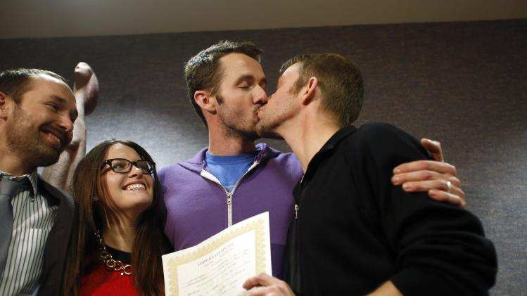 The first gay couple to be married in Utah, Michael Ferguson and his husband Seth Anderson, kiss as Blake Ferguson and his girlfriend Danielle Morgan watch after the pair married at the Salt Lake County Clerks office in Salt Lake City, Utah