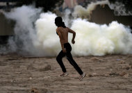 A masked Bahraini anti-government protester carrying stones runs toward riot police firing tear gas, birdshot and rubber bullets during clashes after the politically charged funeral for a teenager in Muharraq, Bahrain, on Saturday, Nov. 10, 2012. Bahrain's main opposition group says the kingdom's paramilitary national guard is deploying to back up police as authorities try to quell rising political violence. (AP Photo/Hasan Jamali)