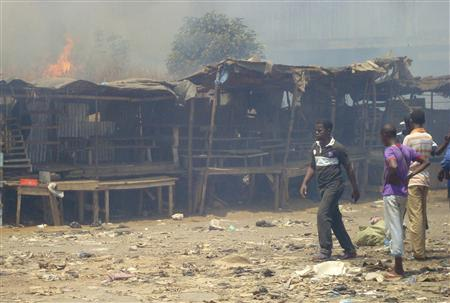Men stand and watch as a fire rages in the background during clashes between rival gangs in Marche Madina, in Conakry March 1, 2013. REUTERS/Saliou Samb