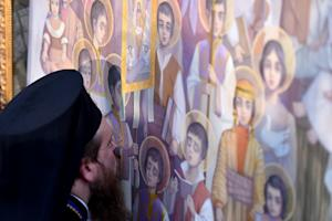 A cleric kisses an icon during a canonization ceremony…