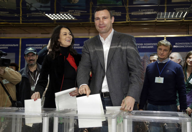 Chairman of the Ukrainian democratic opposition Ukrainian Democratic Alliance for Reform Party and former boxing champion Vitali Klitschko, centre right, and his wife Natalia cast their ballots, at a polling station during parliamentary elections in Kiev, Ukraine, Sunday, Oct. 28, 2012. Ukrainians are electing a parliament on Sunday in a crucial vote tainted by the jailing of top opposition leader Yulia Tymoshenko and fears of election fraud. (AP Photo/Efrem Lukatsky)