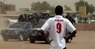 """An image grab taken from AFPTV shows a Sudanese youth wearing a football jersey as he observes riot policemen taking position outside the Wad Nabawi mosque in Khartoum's twin city of Omdurman. Sudanese police on Friday """"attacked"""" with tear gas and rubber bullets as demonstrators gathered at mosques for weekly anti-regime protests sparked by inflation, a rights group said. (AFP Photo/)"""