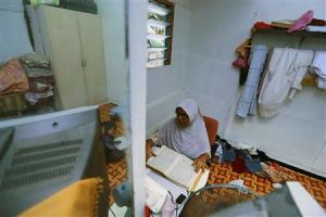 A Rohingya woman reads the Koran in her rented house …