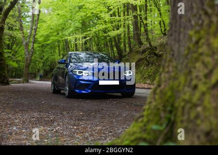 Blue Sedan In The Vacation Zone Under The Rain In The Forest Front Lights On Stock Photo Alamy