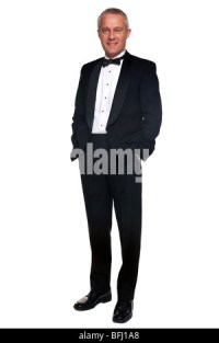 A mature male wearing a black tuxedo and bow tie raising a ...