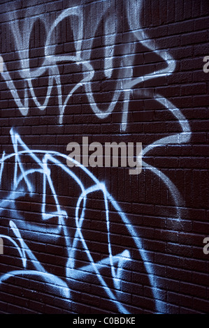 A graffiti spray painted brick wall using red black and