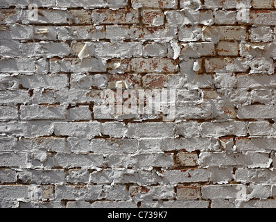 old paint peeling brick wall with spray painted question