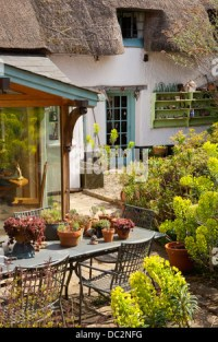 Cottage garden patio with metal table furniture and ...
