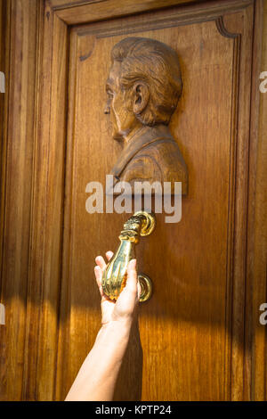 A Hand Holding A Door Handle Of A Traditional Wooden