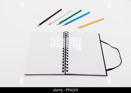 empty open sketchbook and colored pencils on wooden table