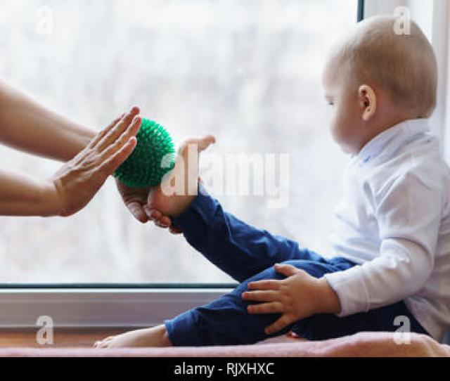 Prevention Of Flatfoot Disease  C2 B7 Mother Makes Foot Massage To Boy Woman Holding Massage Ball In Hand Son Sits