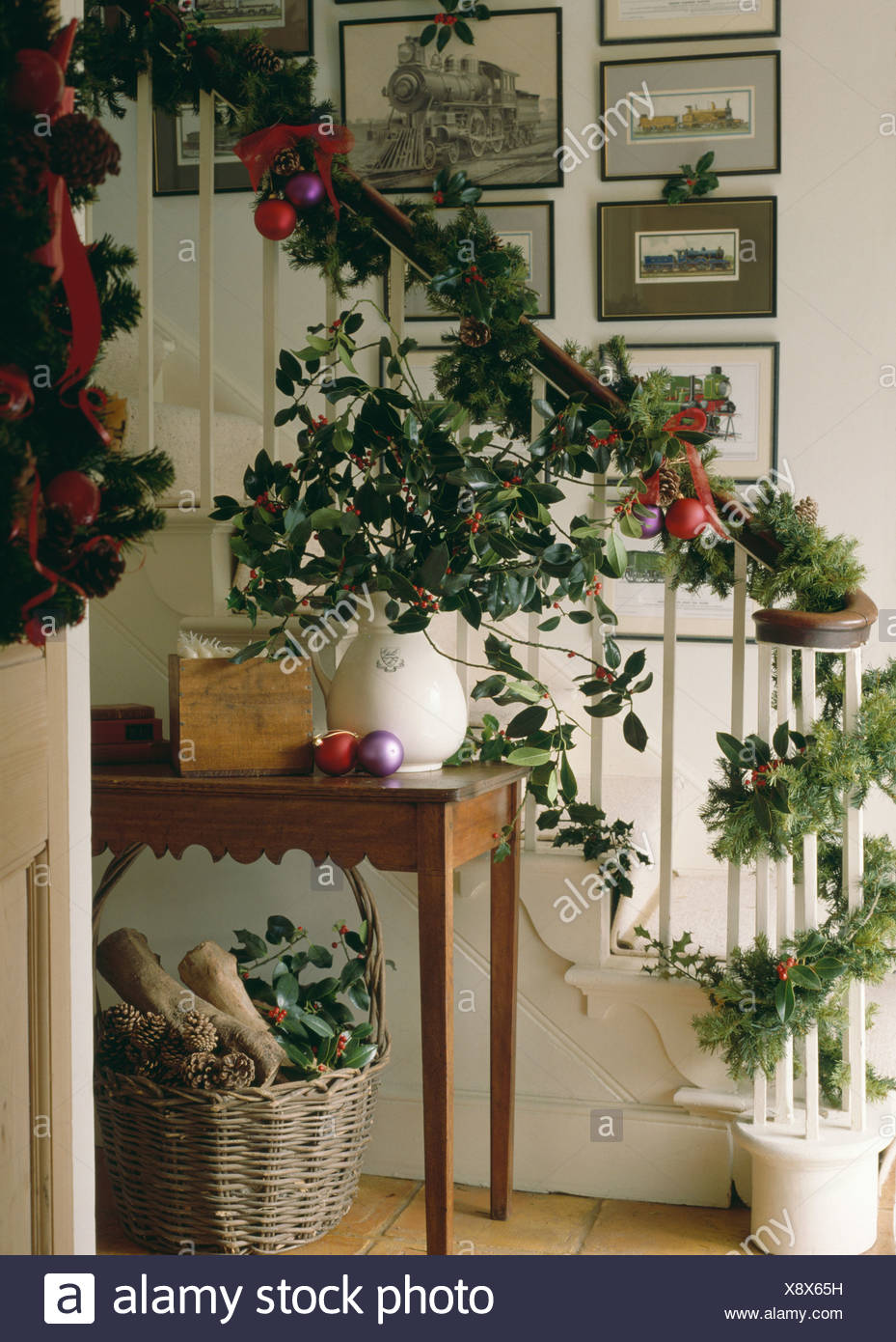 Garlands Of Holly And Ivy With Conifer Branches Decorating Staircase At Christmas Jug On Hall Table