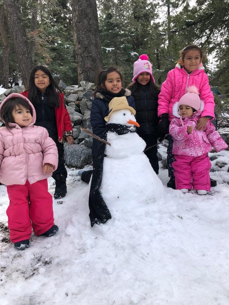 girls building a snowman