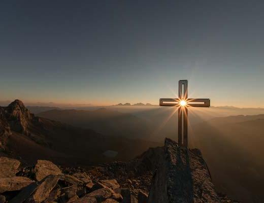 Croix au soleil levant, dans le roc de la montagne - Photo by eberhard grossgasteiger on Unsplash