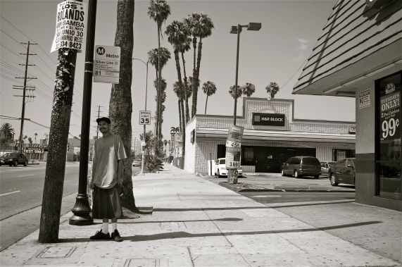A man waits for a bus in the shade of a telephone pole on Figueroa Ave., just north of 85th St. Sahra Sulaiman/Streetsblog L.A.