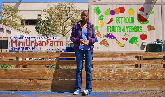 Nina, an intern with Community Services Unlimited, stands in front of the mini-urban farm at Normandie Elementary. Sahra Sulaiman/Streetsblog L.A.