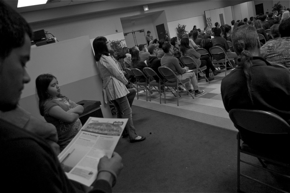 A young boy reads about the practice of fracking at the emergency community meeting held last Saturday at Holman Church. Sahra Sulaiman/LA Streetsblog