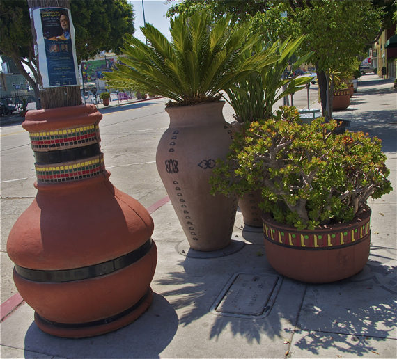 Planters, thatch-wrapped poles, and hanging planters (out of frame) that grace Degnan and other streets in Leimert Park Village.