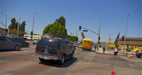 Cyclists battle for space near Crenshaw and Exposition. One takes his chances in the street while the other opts for the safety of the sidewalk. Sahra Sulaiman/LA Streetsblog